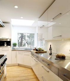 Luxury Kitchens Design With Stainless Steel Countertops With White Wall Cream Cabinet Oven Table Stove Glass Window Lamps Wooden Floor