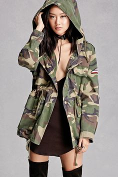 "A woven hooded utility jacket featuring a camo print, various patches including ""Space Is My Home"", a sequined rocket on the back, a zipper and a snap-button front, four flap pockets, long sleeves, and drawstrings at the waist and hem. This is an independent brand and not a Forever 21 branded item."