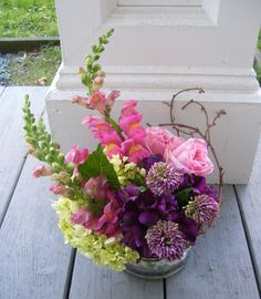 """Centerpiece incorporating pink snapdragons, green hydrangea, bullet allium, purple alstromeria, """"O'Hara' roses and vine.  Roberts Flowers of Hanover, Hanover, NH"""