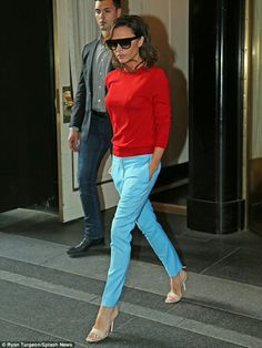 So she doesn't only wear black! Victoria Beckham leaves her NYC hotel in vibrant red top and blue trousers