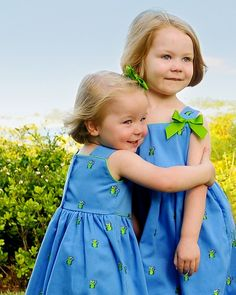 Two sisters in bright blue summer sundresses.