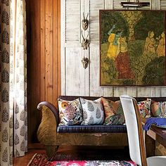 On the dining room wall, a large framed Indian print and roe deer antlers hang on a whitewashed screen made of old shutters. | SouthernLiving.com