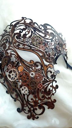 This mask was inspired by the concept of a version of Gaston Lerouxs classic The Phantom of the Opera (the inspiration for the famous musical) staged entirely in a steampunk motif. The Phantom in the novel is an inventor; why would he not remain such in a steampunk-version of this world? This intricate metal laser-cut mask was hand-painted with copper enamel in a quick brush coat to give it an aged appearance. Metal gears were individually chosen and wire-wrapped to the frame to give the…