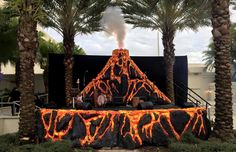 A volcano stage backdrop display with realistic lava made from insulation and spray foam, carved with Hot Wire Foam Factory tools. Dinosaur Train Party, Dinosaur Garden, Dance Party Birthday, 3rd Birthday, Train Party Decorations, Tiki Party, Beach Party, Foam Factory, Halloween Backdrop