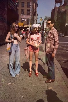 1970's Street Scene - Note the Shaggy Hair and Flared Pants on the left-side girl, and the short top and wedges on the other. Notice the background people, too.
