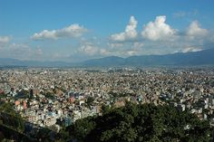 The ancient settlement of Kathmandu as viewed from Swayambhunath Hill, sunny day with a few clouds, trees, ring of mountains, Kathmandu, Nepal
