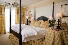 Extra high bead board wainscoting, a vintage chandelier and an Amy Howard four poster bed add to the charm of this master bedroom.