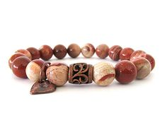 Beautiful women's beaded stretch bracelet featuring 10mm red bend jasper beads and antiqued copper focal bead with a heart charm.