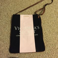 "VS Cross Body Bag VS cross body bag. Light pink and black with pink letters. Brown faux leather adjustable strap. ""Victoria's Secret- London •New York • Paris."" Never used, but has discoloration from storage. Feel free to ask questions. Offers are welcome  Victoria's Secret Bags"