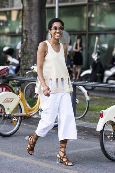 Tamu McPherson in the best color combination for the summer, Stella McCartney knit top, Cos jeans, and Miu Miu sandals.