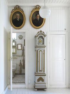 Hallway with clock & portraits by Stellan Herner Elle Interior, Sweden.