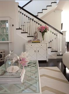 Love the coffee table in this airy space. Also love the dark banister and floor on the stairs