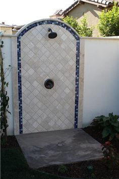 Beautiful outdoor shower for guests to rinse off after swimming. Love how the arch, color, and the blue tile reflect the architecture of the Spanish-style home. Design by Scott Cohen of The Green Scene in CA. Get the details on this project at http://www.landscapingnetwork.com/los-angeles/thousand-oaks-party-backyard.html