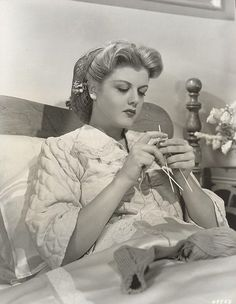 A young Angela Lansbury knitting socks in bed.  ...I do this now, but my makeup and hair gave up hours earlier.
