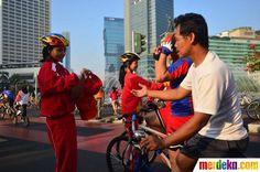 Sejumlah atlet membagikan pin dan topi kepada pengguna jalan di Bundaran Hotel Indonesia (HI), Jakarta Minggu (8/7).
