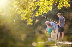 Boy, father and grandfather fishing in lake