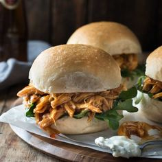 Chicken sliders made in the SLOW COOKER cooked in an awesome sweet and mildly spicy Buffalo sauce!