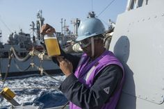 MEDITERRANEAN SEA(Nov.2, 013)Gas Turbine Systems Technician (Mechanical) 1st Class Fred Spaulding inspects fuel sample while refueling Arleigh Burke-class guided-missile destroyer USS Stout (DDG 55) during replenishment-at-sea with Military Sealift Command fleet replenishment oiler USNS Leroy Grumman(T-AO 195).Stout on scheduled deployment supporting maritime security ops & theater security cooperation efforts in US 6th Fleet area of responsibility.(USN Mass Comm Spec 2nd Class Amanda…