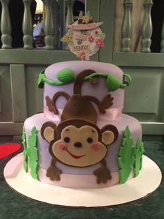 Monkey baby shower tiered cake for baby girl. Fondant monkey, leaves and vines.
