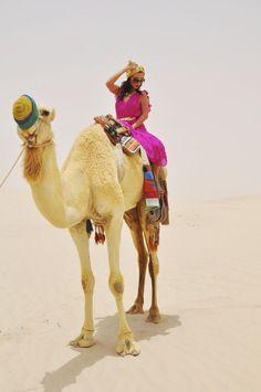 Aureta looking fab riding a camel in Dubai.
