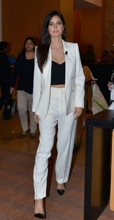 Bollywood beauties are known worldwide, not only known for their acting chops, but also for their superb style and fashion sense. This fact has only been reinstated by the queen of hearts - Katrina Kaif, who was recently seen at an event in Grand Hyatt wearing a white formal suit with classy gold buttons over a black crop top. She adorned no jewellery except for an elegant black brooch pinned to one side. She completed this suave look with black pumps and straight hair.