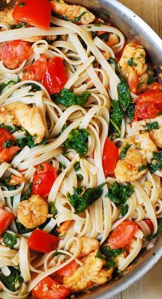Shrimp pasta with fresh tomatoes and spinach in a garlic butter sauce