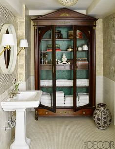 A china cabinet repurposed as a linen closet next to an oval mirror, gold wall sconces, and white pedestal sink.