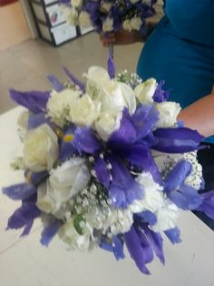 Bridesmaid bouquet with iris, carnations and roses with babies breath.