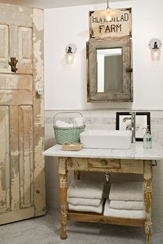 A vintage table becomes an unexpected base for a rectangular vessel sink; other distressed elements include the weathered medicine cabinet and salvaged door. Subway tile, marble, and a single-stem faucet mix in for a rustic-meets-sleek look. | Photo: John Ellis