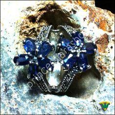 """Anillo realizado en plata de ley 925 con piedra semipreciosa de zafiro y marcasitas. (nº13) El ZAFIRO es una hermosa gema azul que deriva de la palabra griega sappheiros y significa """"la piedra más bella"""". Suele ser de color añil, pero también hay tonos azules más claros o azul oscuro semejante a la tinta. Se compone de restos de titanio y hierro. Los egipcios la llamaban """"piedra de las estrellas"""" relacionada con Maat, la diosa de la verdad…"""