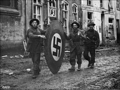 Picture dated February 1945 showing three British soldiers rolling a large wooden swastika along the streets of Kranenberg after British and Canadian troops under the command of Marshal Montgomery fought through the outer defences of the Siegfried line and moved into the Reichswald Forest. From L to R: Mc Ivor of Glasgow, W. Harton of Durham and D. Mill of Dumbartonshire.