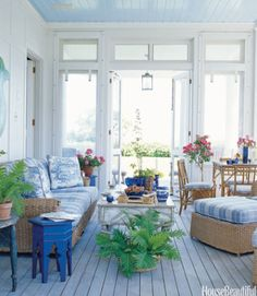 Designer Paula Perlin and architect Mark Ferguson created this idyllic blue porch for a Martha's Vineyard home. The sky blue ceiling—Morning Glory by Benjamin Moore—makes for an unexpected, soothing touch. The Walters Wicker Seagrass sofa and armchairs are covered in a Brunschwig & Fils cornflower blue and white plaid.