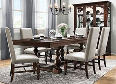 """Create a classically beautiful dining room with the Halloran 7-piece dining set. Traditional features, like its trestle-style table base and upholstered chairs with nailhead trim, make this set look impeccably elegant. It's wonderful for all occasions, from weeknight meals to holiday feasts. Just pop in the 20"""" extension leaf when your guests arrive, then stow it away inside the table when they leave."""