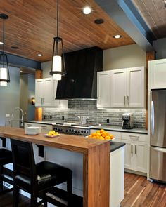 Black barstools, countertops and a range hood create contrast against the white cabinets and light gray walls in this contemporary kitchen. A solid piece of Douglas fir is raised above the countertop on the kitchen island, providing a spot for casual dining. The wood paneled ceiling, which coordinates with the island and flooring, brings warmth to the dynamic space.