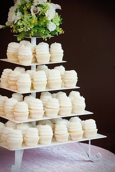 Gigi's Cupcakes wedding reception cupcake stands...I love that they added flowers to the top!