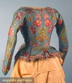 """LADIES SILK BROCADE BODICE, 1780s Go Back Lot: 767 April 2006 Vintage Clothing & Textile Auction New Hope, PA Figured aqua silk brocaded w/ multi-colored floral designs, ruched cream silk gauze ribbon, homespun linen lining, B 34"""", W 23"""", Sh-W 15"""", excellent."""
