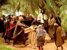 Free Bible images of Jesus riding triumphantly into Jerusalem on a donkey while the crowds wave palm branches and shout, 'Hosanna'.