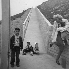 In December of 1955 our family went to California to visit my grandma Wilkins and Uncle Torchy (Torrey Wilkins). While on the ramp going towards the beach my grandma must have run into some bad luck with her shoe. She looks like she's about to drop my brother Jim who is in her arms! I love the look on Torrey's face. I also like seeing my confused look as I watch my grandma struggle with her shoe. Or maybe I was worried about my baby brother!