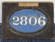 "LOT 545: A cast iron number plate ""2806"". Approx. 15 cms wide. (Broken across one fixing point). Set to a wooden board with typed paper label ""Plant Number From Forge of Ipswich Old Loco Shed"". Est. £20 - £30. Coming up in our #Silver #Jewellery #Toys and #Railwayana #Auction on Thursday 25th May.To include #Watches #Collectables #Pictures #China & #Antique #Furniture #May25 #whittonsauctions #Honiton #pin"