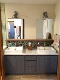 bathroom double vanity vessel sinks chrome fixtures double mirror river rock backsplash