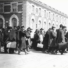 Immigrants carrying suitcases at Ellis Island, early 1900s.  Ellis Island, which opened in 1892 kept the administrative records and allowed immigration officers to check for diseases and to verify that each immigrant had at least $25 and had someone to meet them upon arrival, an effort to make sure that they would not become a ward of the state.