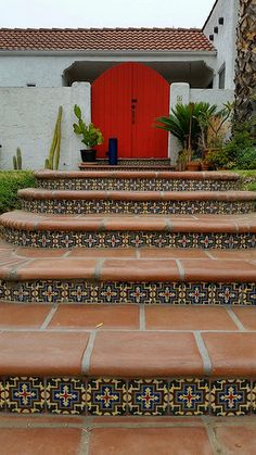 The red doors at top of stairs really make the Saltillo Tile and decorative ceramic tiles really pop!