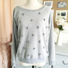 Gray Jewel Embellished Sweatshirt Purchased years ago but never worn. I think from hanging it my closet one of the jeweled petals got lost along the way. Super comfortable, refined lounge wear! Janice Sweaters