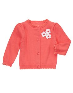 Super soft sweater cardigan is accented with pretty blossoms and scalloped trim.