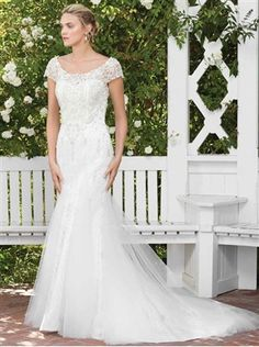 Gloriosa is a decorative and timeless option for the upscale modern socialite. The heavily beaded bodice and scoop neck shape builds into a wide keyhole back, while tulle godets provide textural difference and volume for the skirt.