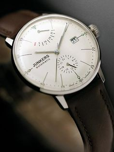 Junkers 6060-5 Bauhaus watch comes with a power reserve meter at 12:00 and a 24 hour sub-dial at 6:00. Inside is a modified 26-jewel Citizen self-winding movement with a silver rotor that is viewable via an exhibition case back. Hesalite crystal.