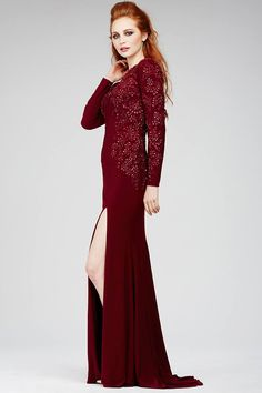 Stunning long sleeve jersey dress features a jewel neckline along with a leg slit and unique applique design