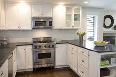 subway tile, white cabinets, dark counter, medium dark floor, stainless appliances