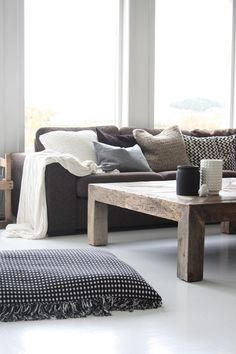 Inspiration: Cozy dark grey sofa, layered with white and grey cushions. A white floor and walls lift the whole look.