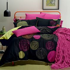 """Brilliant colour and lavish embroidery ensure that Jasmine is no shy, retiring wallflower! Colours of hot pink, orange and chartreuse """"pop"""" on the black background and are complemented by the quilted and embroidered accessories. The quilt cover has a plain chartreuse reverse and button closure."""